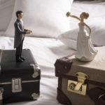 статуэтки жениха и невесты на разных чемоданах на кровати