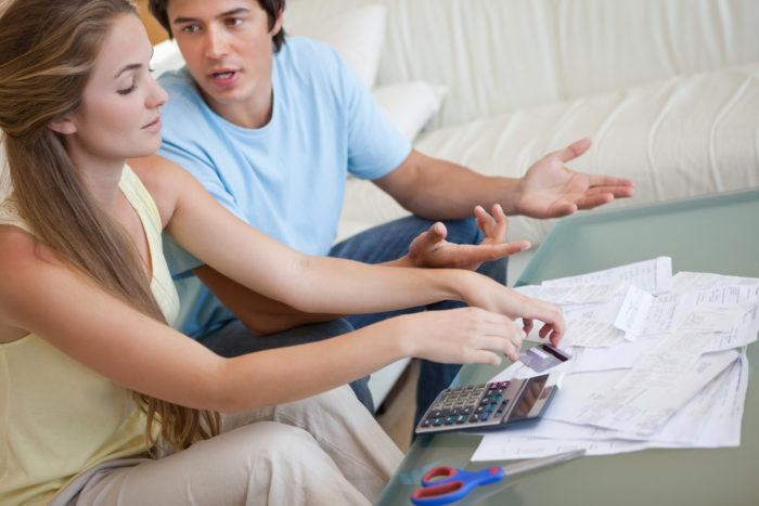 парень с девушкой на диване, документы, ножницы, калькулятор и карточка на столе