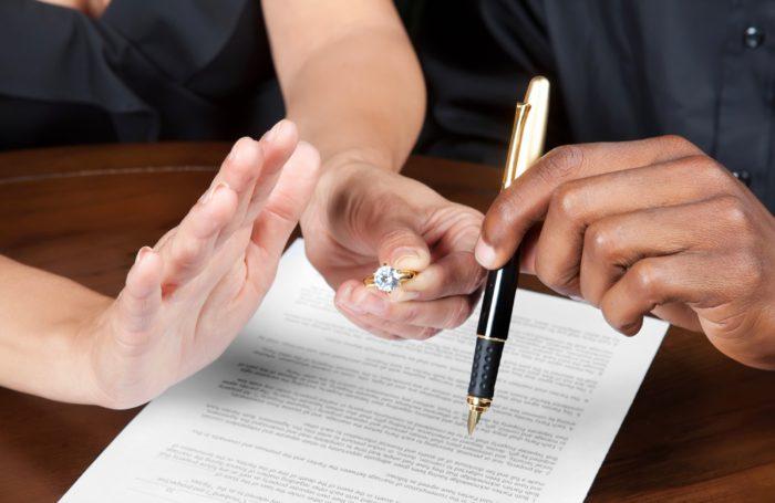 кольцо и ручка в руках, документ на столе