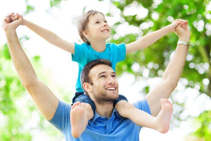 мальчик сидит на плечах у отца