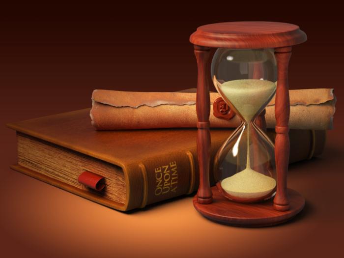 песочные часы и сверток из бумаги, скрепленный печатью, на книге на столе