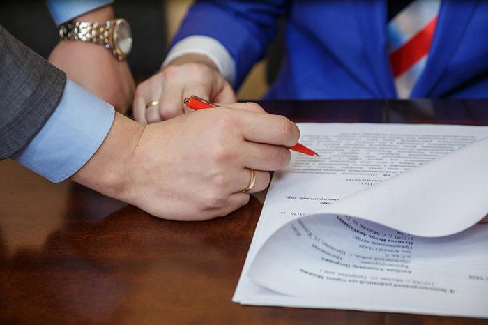 подпись документа ручкой, руки на столе