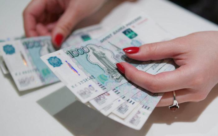 российские деньги в руках с ногтями, покрытыми красным лаком