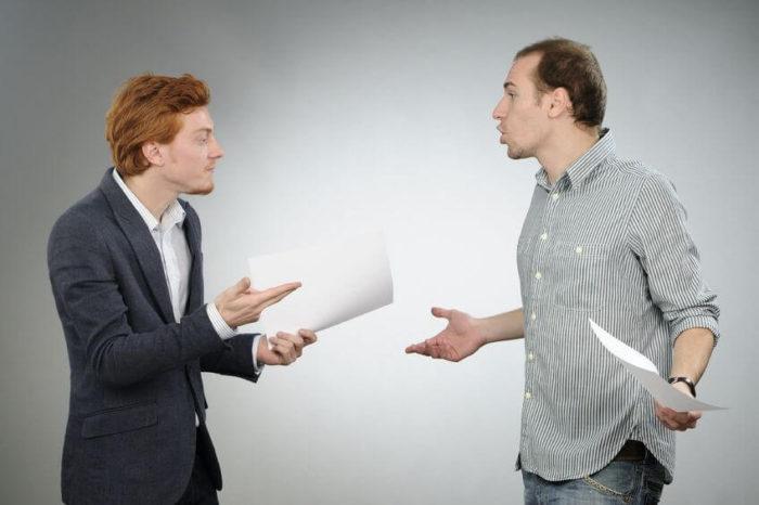 два мужчины разговаривают и держат в руках документы