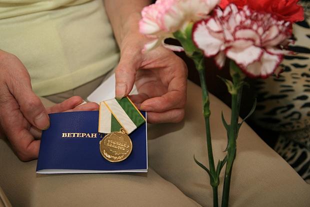 синее удостоверение и медаль ветерана труда в руках, разноцветные гвоздики