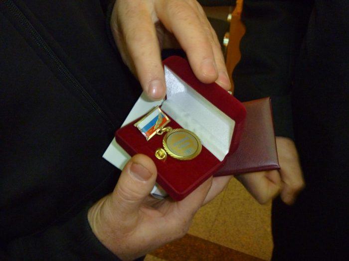 медаль ветерана труда РФ в красной замшевой шкатулке в руках