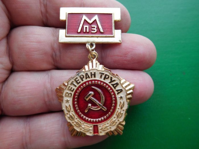 красно-золотая медаль ветерана труда в руках