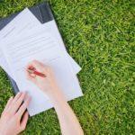 заполнение документов на черной папке на траве