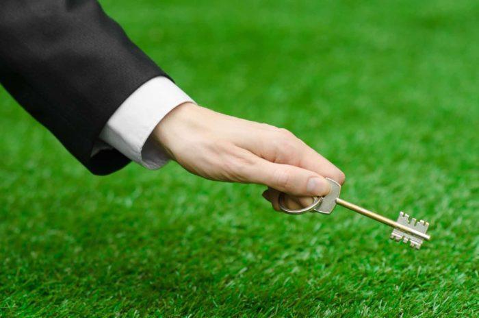 ключ в руках и зеленая травка на фоне