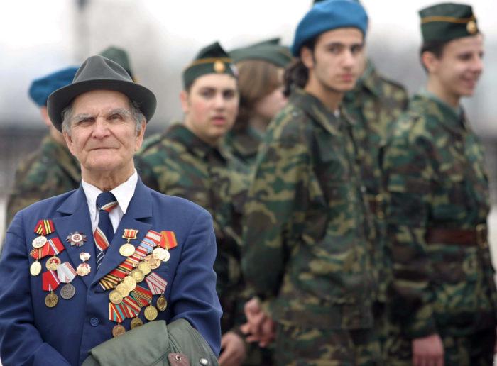 ветеран войны в медалях и солдаты на фоне