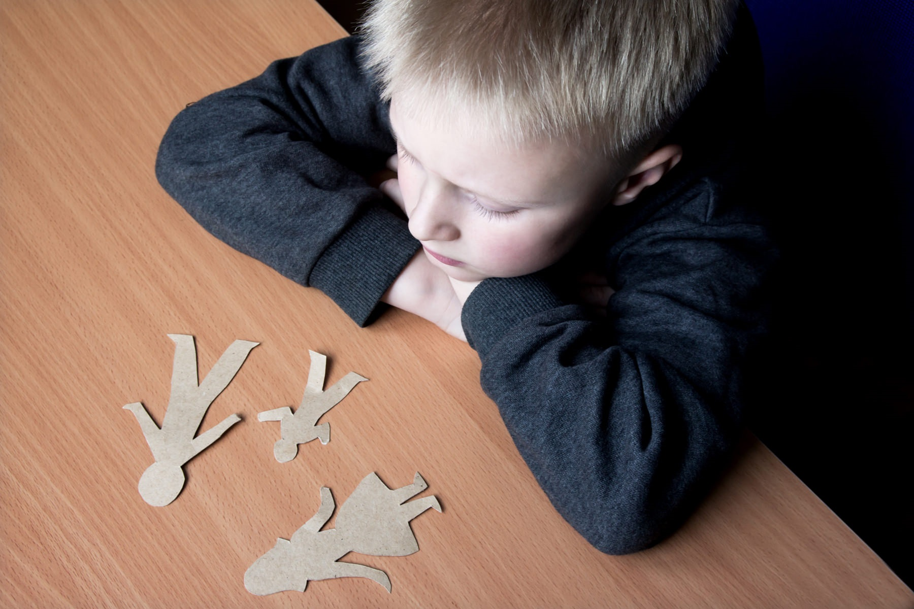 грустный ребенок и бумажные фигурки на столе