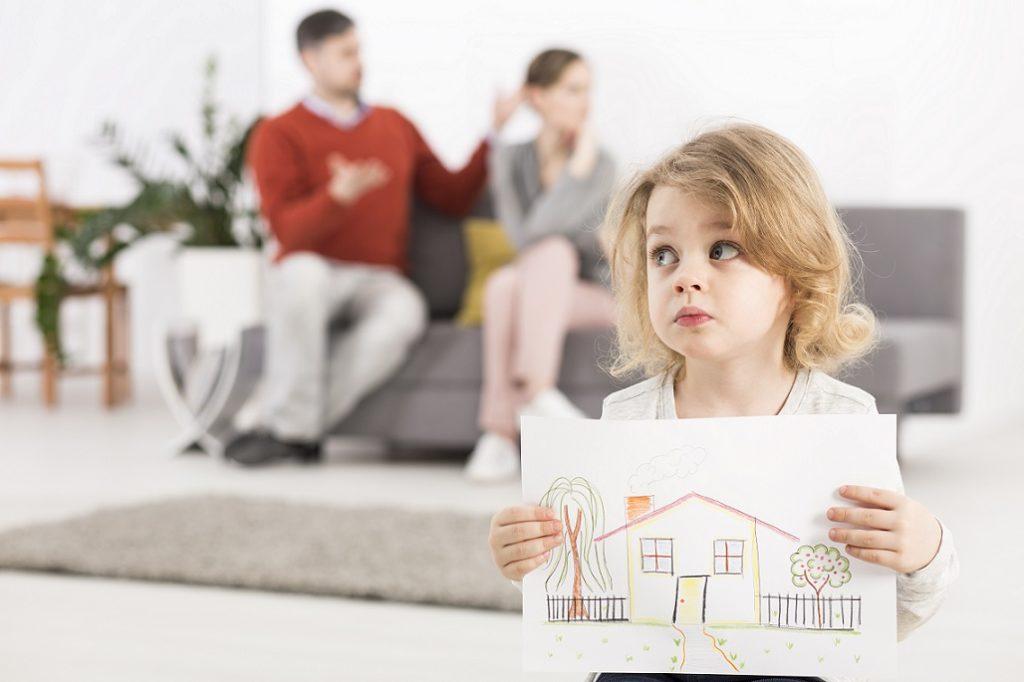 маленькая девочка с рисунком дома в руках