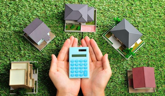 дома и калькулятор в руках