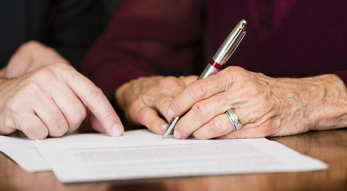 Пожилая женщина подписывает документ