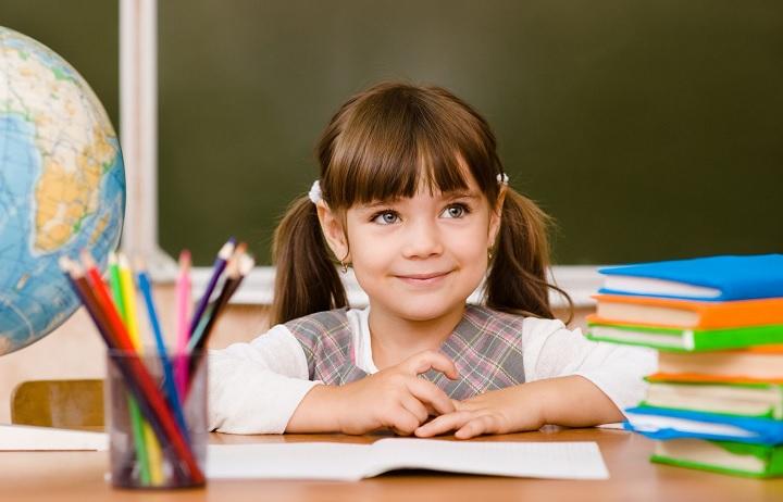 Девочка сидит за партой в школе