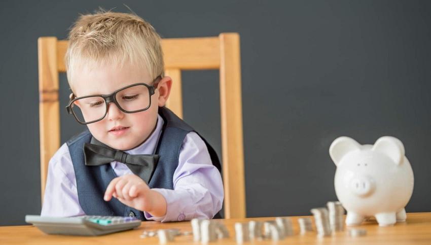 Мальчик считает монеты с копилки
